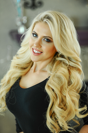 Indoor portrait of young attractive blond woman with glamor make-up and wavy hairstyle.  Looking in to the camera smiling.  Banco de Imagens