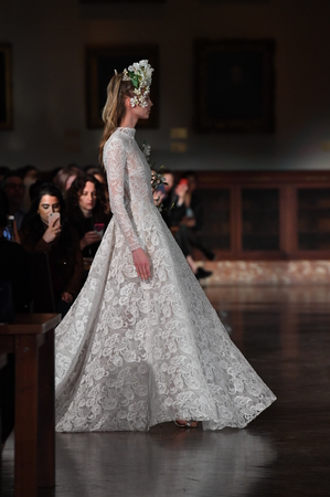NEW YORK, NY - APRIL 12: A model walks the runway wearing Reem Acra Spring 2019 Bridal Collection at the New York Public Library on April 12, 2018 in New York City.