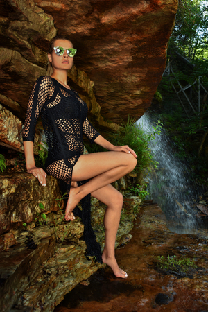 Fashion outdoor photo of sexy beautiful woman in elegant swimwear posing at the rock with waterfall on the background. Stock Photo - 102962207