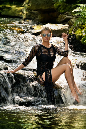 Stunning, sexy blonde female model with perfect body wearing elegant swimsuit posing at waterfalls in the forest.  Stock Photo