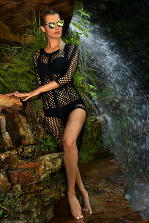 Fashion outdoor photo of sexy beautiful woman in elegant swimwear posing at the rock with waterfall on the background.  Stock Photo