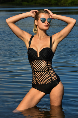 Glamour photo of pretty young woman in fashionable swimsuit posing in the water.