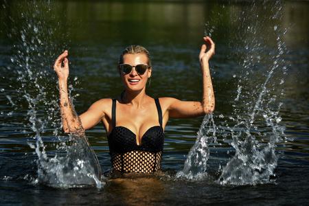Beautiful blonde girl enjoying summer time splashing in the water.