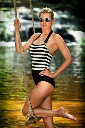 Glamour young woman in fashionable swimsuit and sunglasses posing on the swing with waterfalls on the background.