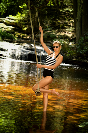Beautiful swimsuit model posing on the swing at the forest lake with waterfalls on the background.