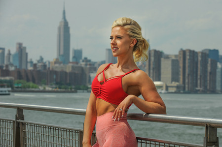 Outdoor portrait of blonde young woman in sportswear. Female sporty and sexy muscular body. Fitness concept. Stock Photo