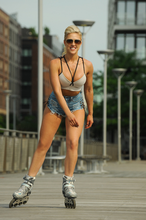 Young, beautiful, sporty and fit girl rollerblading on skates. Stock Photo
