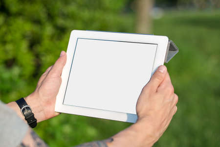 Man with tablet in hands at park photo