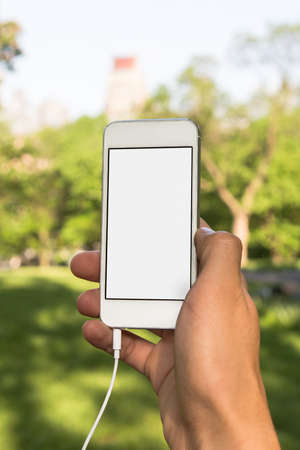 phon: Men in the park with white phon in hand