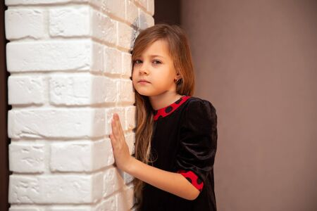 Beautiful cute girl with long hair in black and red dress at white brick wall Foto de archivo - 141067691