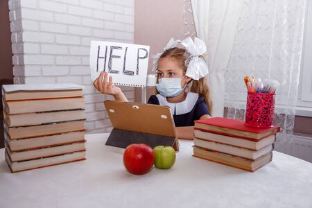 Distance learning online education. girl in a medical mask holds a sign of help. Textbooks and notebooks on the table