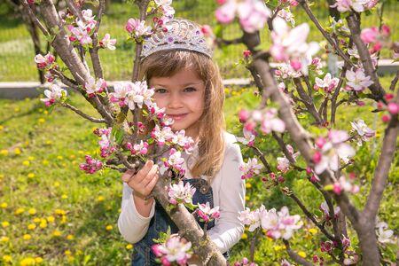 portret Girl little child in crown in spring flower bloom. Enjoy smell of tender bloom sunny day. Sakura flower concept. Gorgeous flower beauty. flower background. Sakura tree blooming. garden. Stock Photo