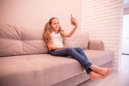 Childhood and technology. Pretty little girl taking selfie by her smartphone Foto de archivo
