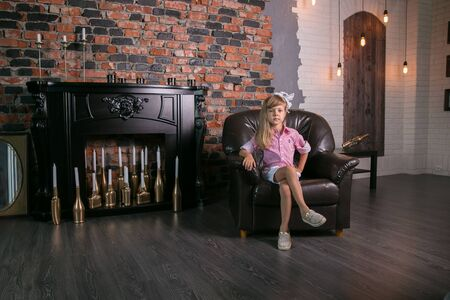 Girl against the background of a vintage-style fireplace. Foto de archivo
