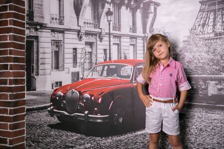 childhood, tourism, travel, vacation and people concept - happy beautiful little girl over eiffel tower in paris background Foto de archivo