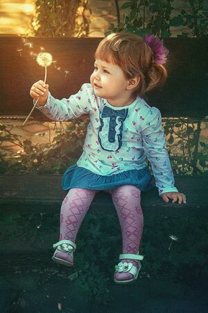 Summer fun, sweet little girl blowing dandelion. girl and dandelion