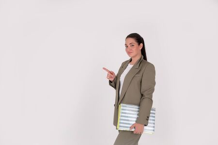 Successful business woman on grey background with copy space. boss in suit and with documents in hand pointing finger and looking away over gray background