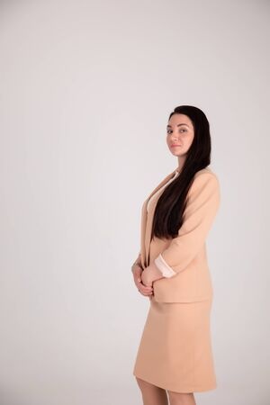 Successful business woman on grey background with copy space. Director in beige strict suit
