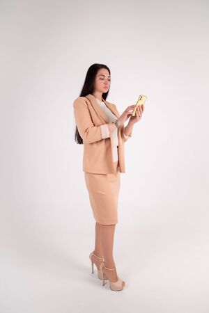 Successful business woman on grey background with copy space. chief in beige strict suit speaks by phone