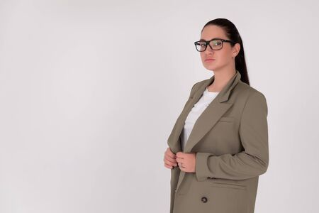 Business woman brunette in green suit and glasses On grey isolated background