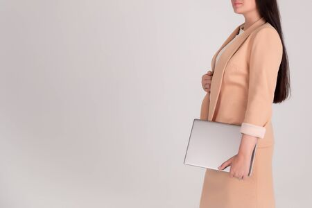Successful business woman without the person on grey background with copy space. girl in beige strict with laptop Foto de archivo