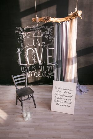 Greeting card Valentine's Day card. The composition of the Valentine 's Day inscription - I love you. Black grey wall with inscription love and lonely chair Foto de archivo