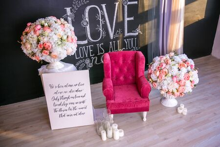 Greeting card Valentine's Day card. The composition of the Valentine 's Day inscription - I love you. Black grey wall with inscription love bouquet of flowers and red chair