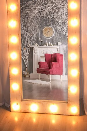 Red chair against background of white fireplace reflected in mirror with yellow light bulbs