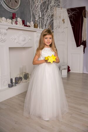 Portrait of cute smiling little girl in princess dress In a beautiful magical interior