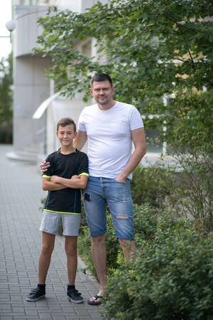 Father and son walking outdoors together in summer on the street Foto de archivo