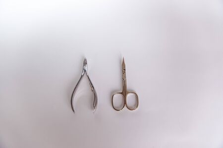 Manicure scissors and nail tongs on a white background. Imagens