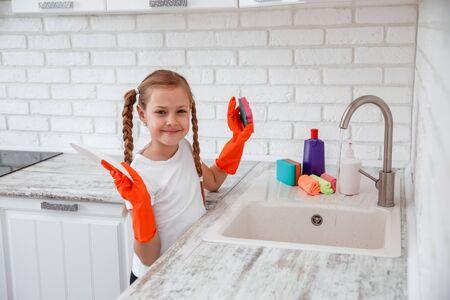 Cute Girl baby in kitchen clean white plate Standard-Bild