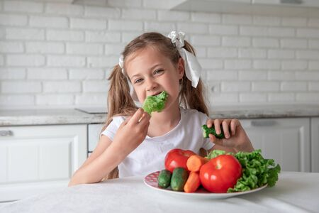 little girl eats vegetables in the kitchen. healthy food. vegetarianism. child eats plant food