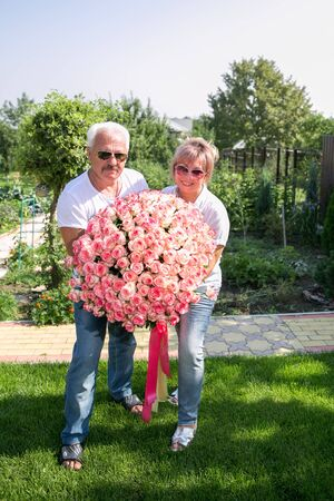 middle aged couple With a large bouquet of flowers