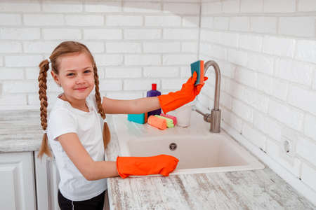 Girl child in kitchen wipes faucet. Chores for children