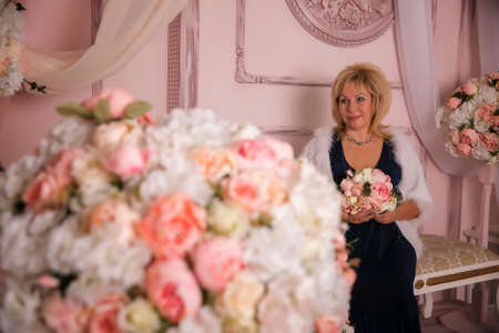Beautiful adult woman, 50, in floral interior