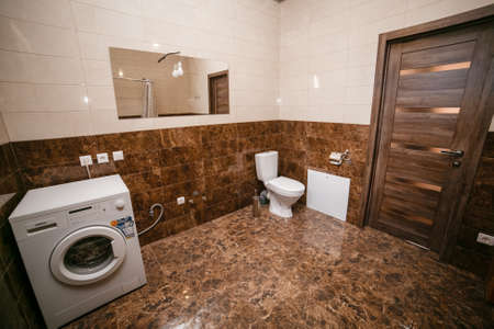 bathroom in brown tones. large room with toilet, bath and washing machine. Russia Imagens
