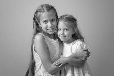 two Happy little sisters. sisters embrace each other. Black and white photo