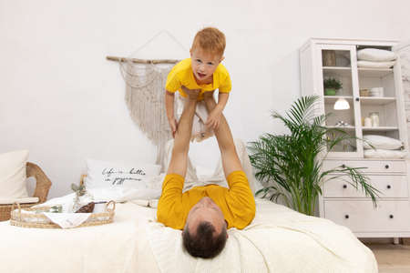 father and little son playing funny game at home, loving happy dad carrying adorable preschool boy pretending flying with hands outstretched, lying on cozy couch in living room. male parent holds a boy in outstretched arms