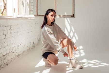 beautiful brunette girl in sportswear sits on the floor