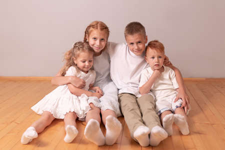 brothers and sisters. children hug. redheads and blondes. 4 children. large family. lots of kids sitting on the floor