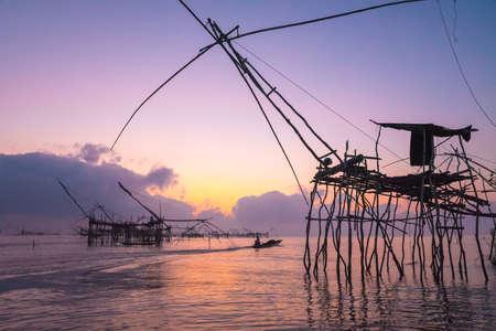 fish net: Silhouette the fisherman in boat near big fish net traps at dawn under romance sky.