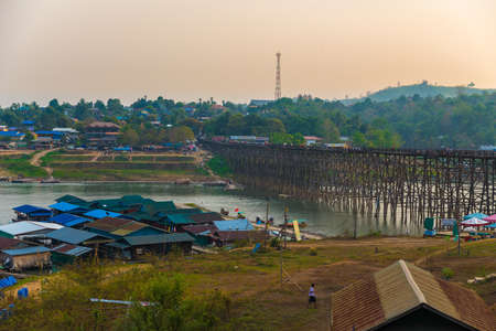 alongside: Under sunset, Mon Bridge of Sagklaburi, Thailand is a attracion. Tourists visit here for look at traditional lifestyle alongside river.