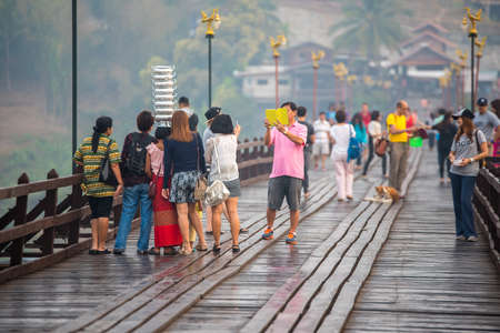 showoff: SAGKLABURI THAILAND- MARCH 11 : Unidentified Mon girl is walking at Mon Bridge showoff herself and selfie with tourists on March 11, 2016 at Mon Bridge.