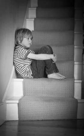 crying child: Sad boy on stairs