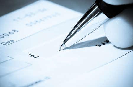 firmando: Cheque libro y la pluma Foto de archivo
