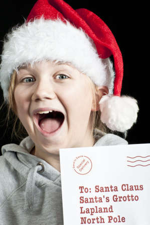 Happy girl in santa hat with letter for santa photo