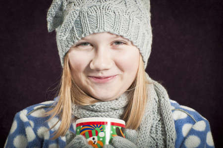 Smiling girl with warm drink photo