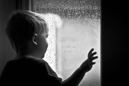 Boy looking at the rain Stock Photo