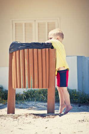 rubbish bin: Boy putting waste in the litter bin Stock Photo